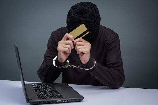 黒い帽子をかぶって、顔を隠す泥棒が灰色で逮捕された