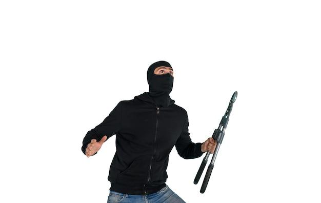 Вор в балаклаве молча крадет квартиры с кусачками в руке Premium Фотографии