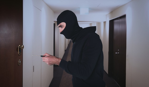 Thief with balaclava tries to open the door of apartment with a key