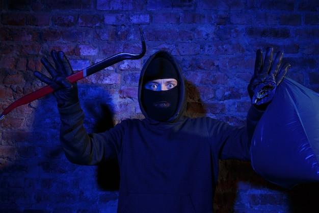 벽돌 벽 근처에 마스터 키와 가방이 있는 도둑