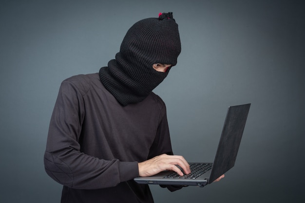 Thieves hold credit cards using a laptop computer for password hacking activities.