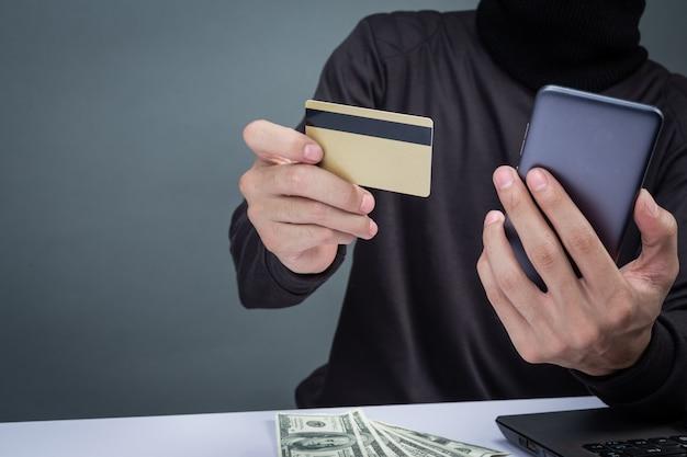 I ladri indossano un cappello nero, tengono il telefono e una smart card su grigio
