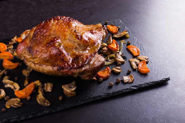 Thigh turkey baked in the oven with spices on black stone background