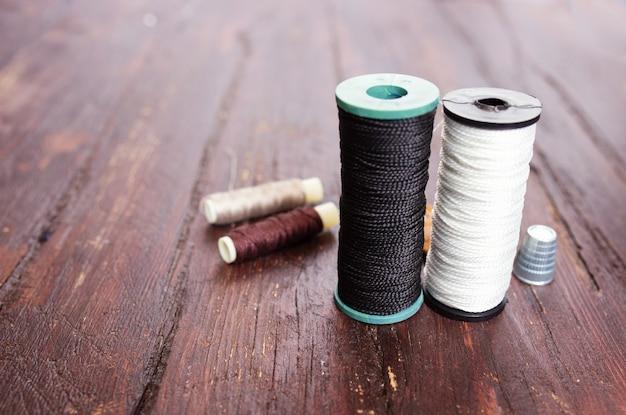 指ぬきと木材の背景にクローズ アップを縫うための針