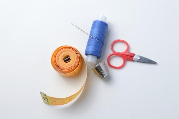 指ぬき、糸のスプール、はさみ、巻尺の針。クローズアップ。