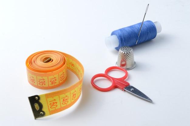 指ぬき、糸のスプール、はさみ、巻尺の針。クローズアップ。 Premium写真
