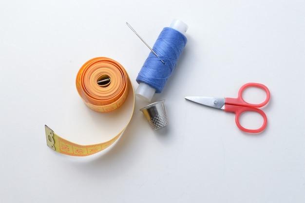 指ぬき、糸のスプール、はさみ、白い背景に巻尺の針。クローズアップ。