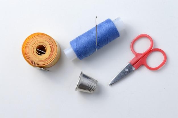 指ぬき、白い背景に糸、はさみ、巻き尺が付いた針。クローズ アップ。
