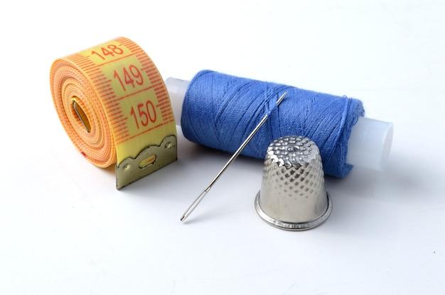 指ぬき、白い背景の上の糸と巻尺の針。クローズアップ。 Premium写真