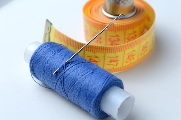 指ぬき、白い背景の上の糸と巻尺の針。クローズアップ。