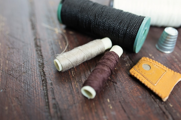 Thimble and needles for sewing close-up on a wood background
