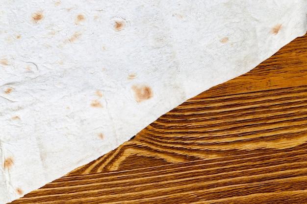 Тонкий запеченный лаваш на деревянном старом столе