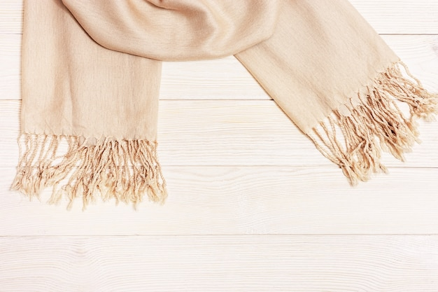 コピースペースと木製のテーブルに薄いベージュの女性のスカーフ