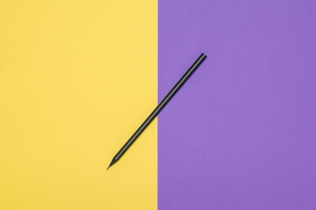 노란색과 보라색 배경에 얇은 검은 연필. 세련된 문구.