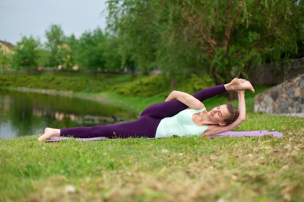 Худенькая брюнетка занимается спортом и выполняет красивые и сложные позы йоги в летнем парке. зеленый пышный лес и река. женщина делает упражнения на коврик для йоги