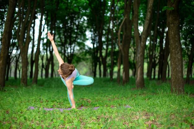 Худенькая брюнетка занимается спортом и выполняет красивые и сложные позы йоги в летнем парке. зеленый пышный лес на заднем плане. женщина делает упражнения на коврик для йоги