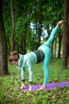 Худенькая брюнетка занимается спортом и выполняет красивые и сложные позы йоги в летнем парке