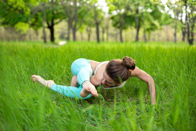 Thin brunette girl plays sports and performs beautiful and sophisticated yoga poses in park.