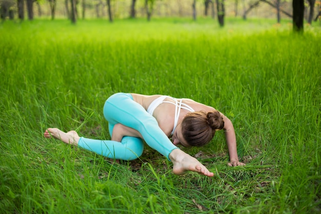 Thin brunette girl plays sports and performs beautiful and sophisticated yoga poses in a summer park