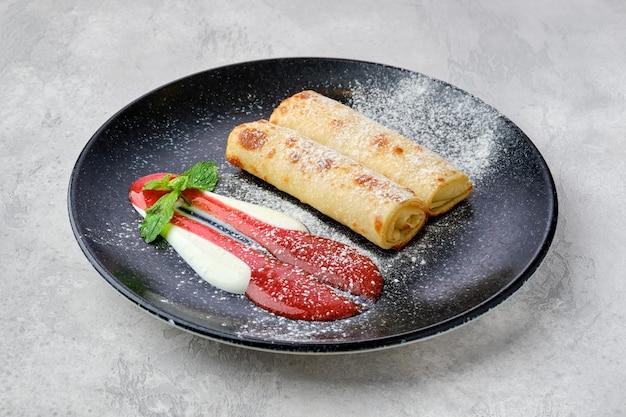 코티지 치즈로 속을 채운 얇은 크레이프와 딸기 잼, 사워 크림 제공