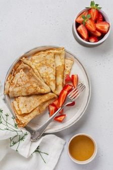 Thin crepes pancakes with cream cheese and fresh strawberry, top view.