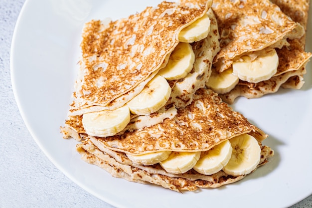 Thin crepes with banana on a white plate.