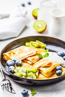 Thin crepes with curd cream, kiwi and blueberries in a black plate.
