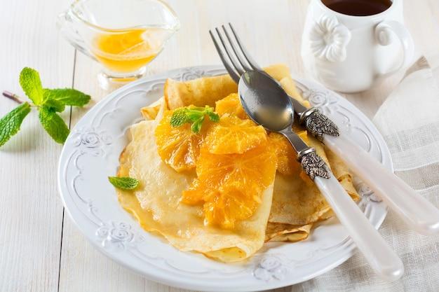 明るい表面での朝食用のオレンジシトラスソースの薄いクレープ。セレクティブフォーカス。