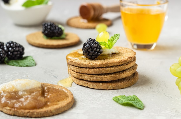 Thin crispy wholegrain crackers with cream cheese, blackberry, grapes, mint and honey.