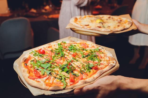 新鮮なバジルの葉をトッピングした薄い生地のピザ。ピザのスライス。手作りの料理