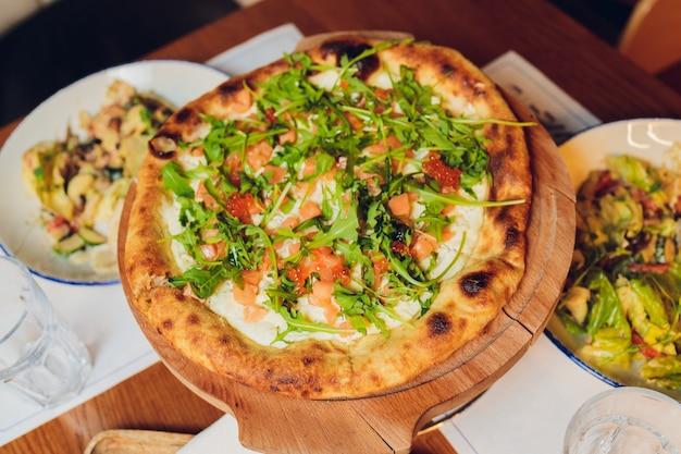 新鮮なバジルの葉をトッピングした薄い生地のピザ。ピザのスライス