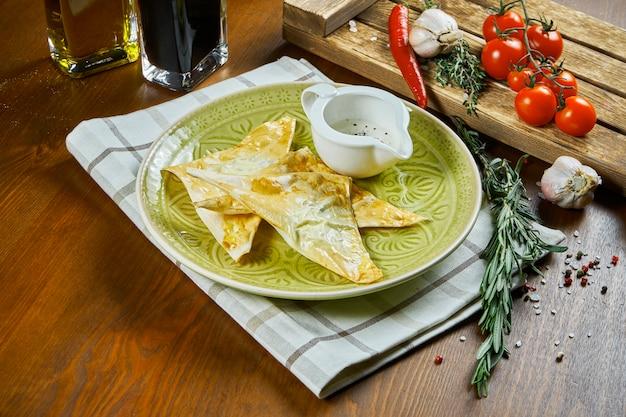 緑の皿に塩漬けのカッテージチーズの詰め物とクリームソースの薄い生地の封筒。おいしい焼き生地。チーズとチェブレク