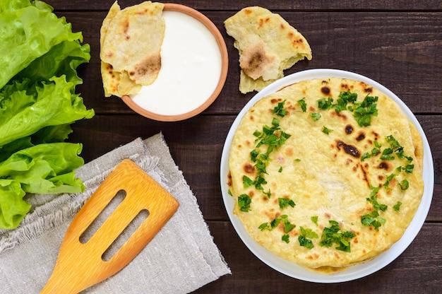 薄いフラットブレッド-暗い木製のテーブルの上の伝統的なアジアのパン。上面図