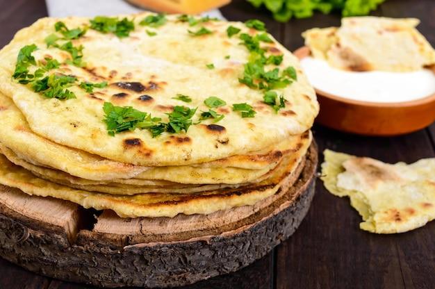 薄いフラットブレッド-暗い木製のテーブルの上の伝統的なアジアのパン。