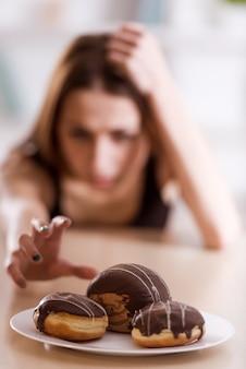 Худенькая девушка отказывается от сладостей, которые есть в белой тарелке.