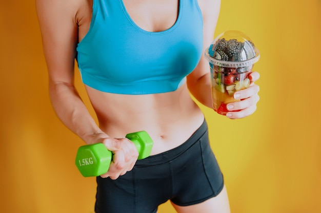 Thin girl with a glass of fruit and dumbbells in her hands