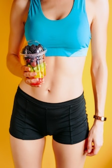 Thin girl with a glass of fruit  in her hands