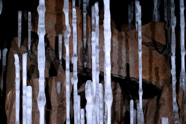 갈색 돌 배경에 있는 동굴의 얇은 높은 얼음 기둥