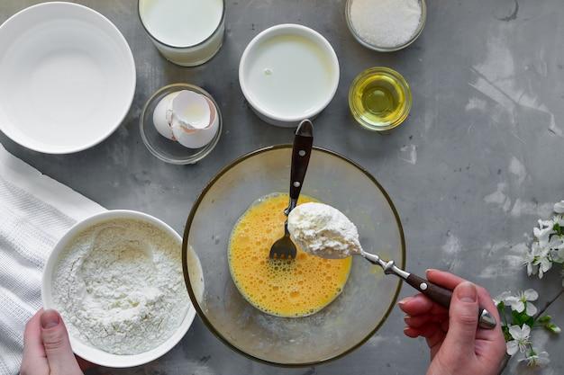 薄い自家製パンケーキ。薄いパンケーキのレシピ。軽いコンクリート面。上面図。伝統的なパンケーキの段階的な調理。材料。料理。フレームの手