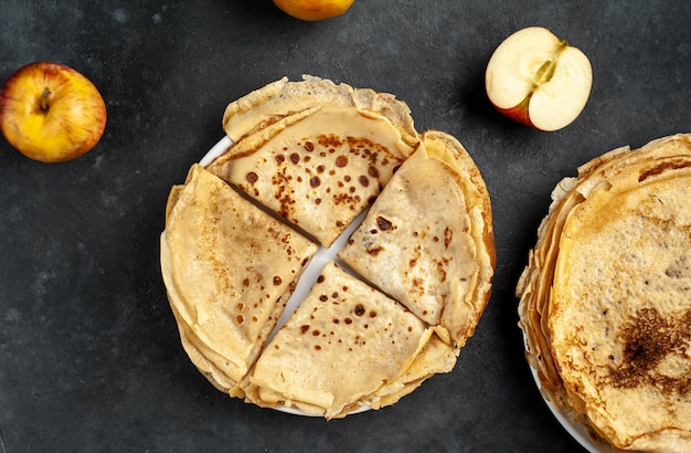 石の背景にリンゴと薄い自家製パンケーキ