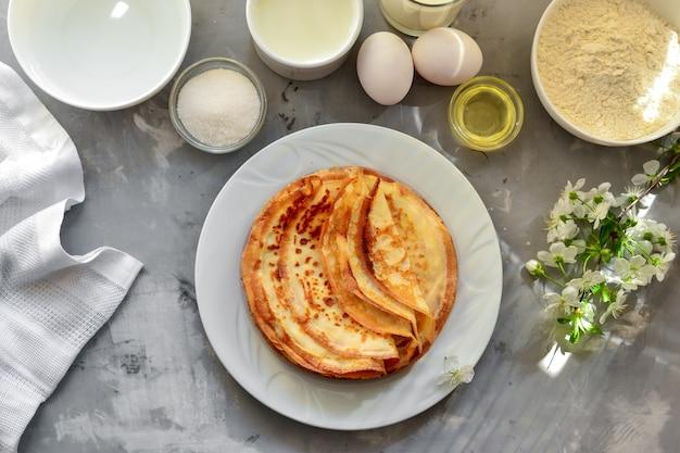 ベリーの薄い自家製パンケーキ、チェリーのパンケーキ。軽いコンクリート面。上面図。おいしい甘い朝食。伝統的な英語とフランスのクレープ。材料。料理。