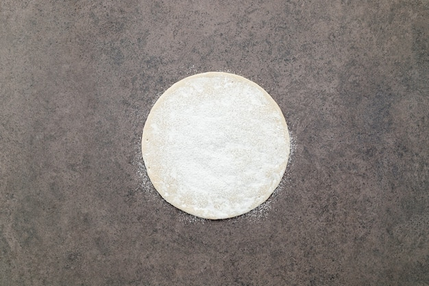 Thin homemade pizza dough with scattered wheat flour on dark concrete background.