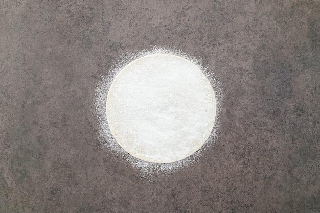 어두운 콘크리트 배경에 밀가루를 뿌린 얇은 수제 피자 반죽.