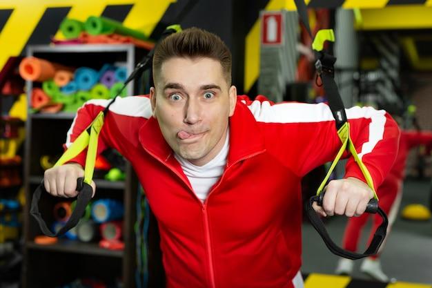 Худой мужчина в красном спортивном костюме тренируется в спортзале, веселится и корчит рожи.