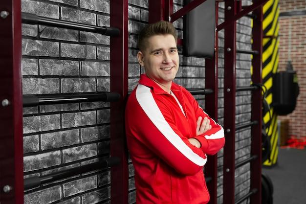 Худой мужчина в красном спортивном костюме позирует у стены спортзала.