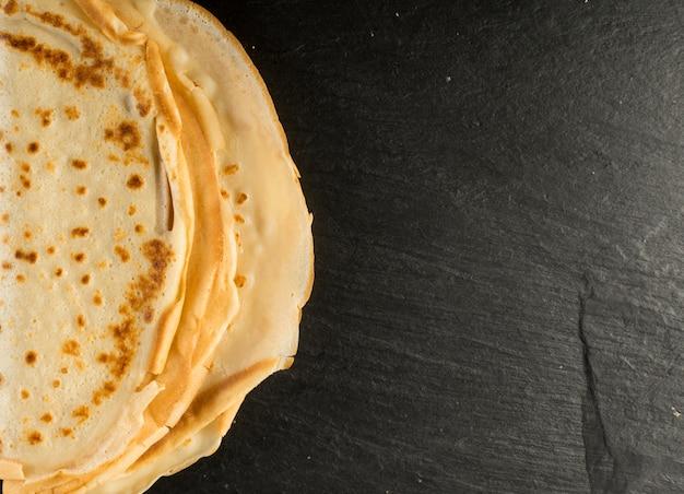 Thin pancakes on black background