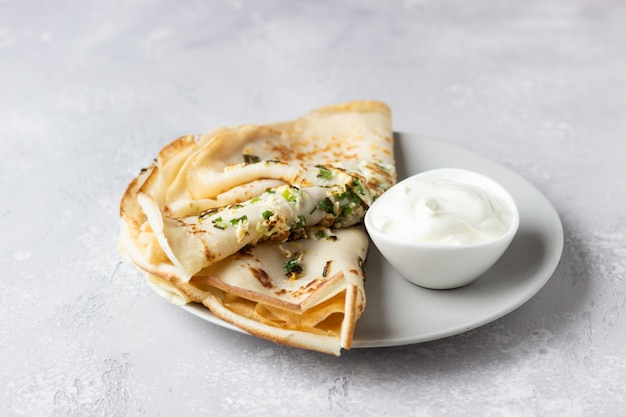 Thin pancakes or crepes with egg, green onion and sour cream