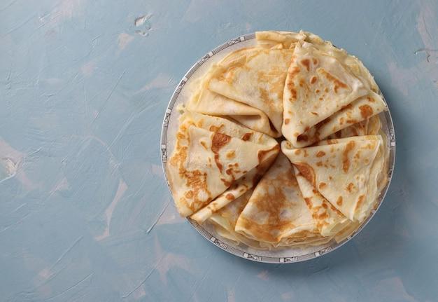 밝은 파란색 배경에 밀가루, 계란, 우유로 만든 얇은 팬케이크. 평면도. 복사 공간