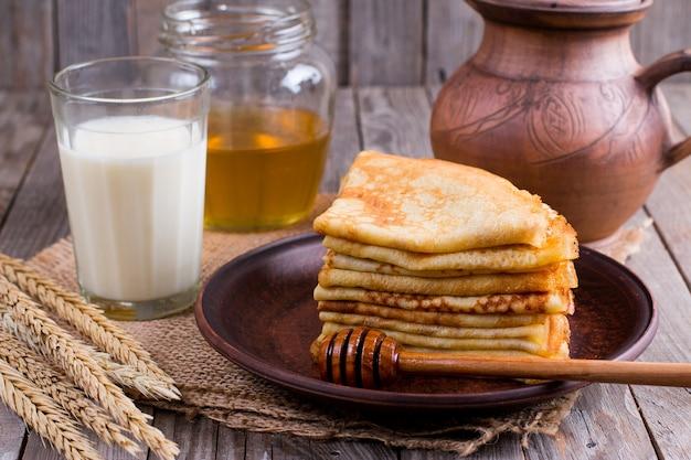 Тонкие блины на тарелке с медом и стаканом молока на деревянном