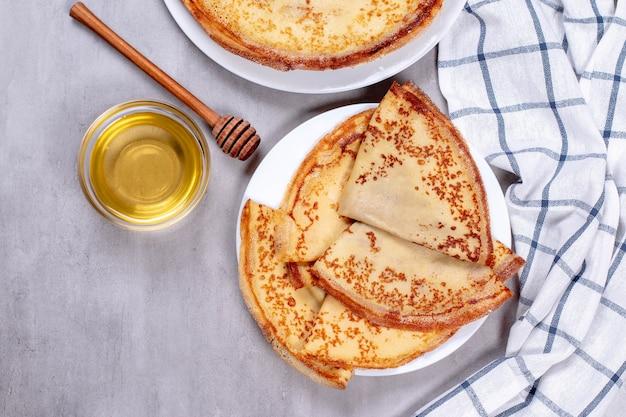 꿀과 하얀 접시에 얇은 팬케이크. 평면도.